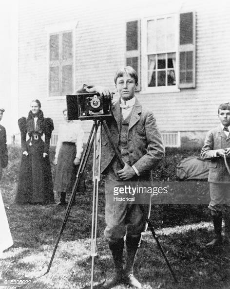 Franklin D Roosevelt stands with his box camera at the Delano homestead in Fairhaven Massachusetts a stopover point en route to his first classes at...