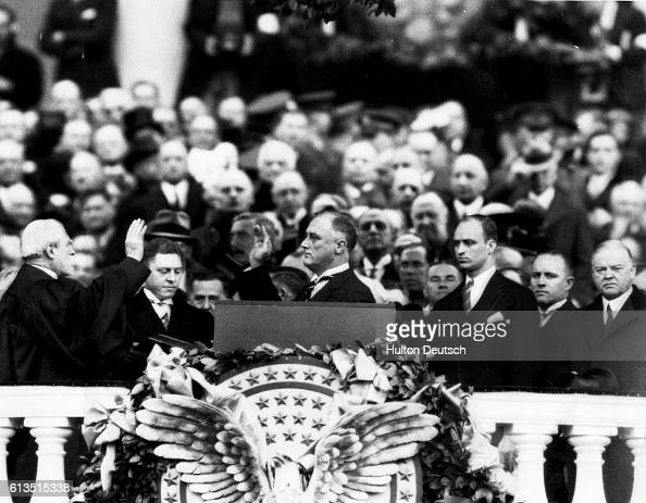 Franklin Delano Roosevelt takes the oath of office from Chief Justice Charles Evans Hughes To the right is Roosevelt's son James and former president...