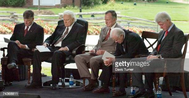 Franklin Graham Billy Graham and former US Presidents George H W Bush Jimmy Carter and Bill Clinton bow their heads in prayer during the Billy Graham...