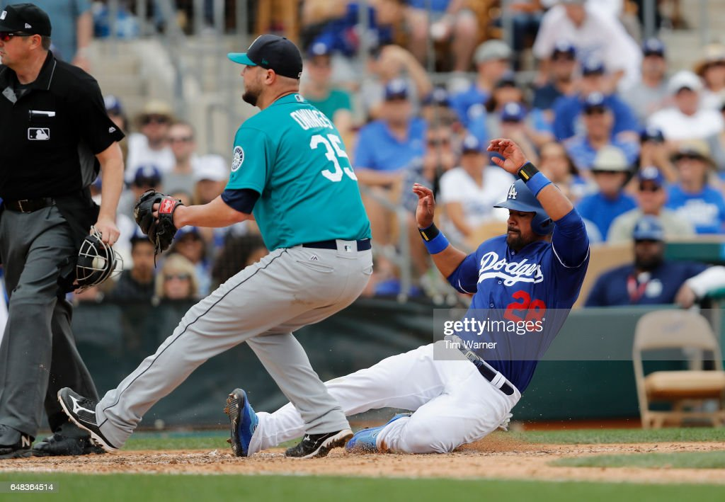 Franklin Gutierrez #28 of the Los Angeles Dodgers scores on a wild pitch covered by Micah Owings #35 of the Seattle Mariners in the sixth inning of the spring training game at Camelback Ranch on March 5, 2017 in Glendale, Arizona.