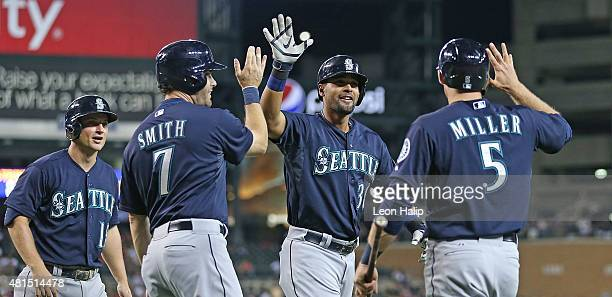 Franklin Gutierrez of the Seattle Mariners celebrates with his teammates Seth Smith and Brad Miller after hitting a grand slam home run in the eight...