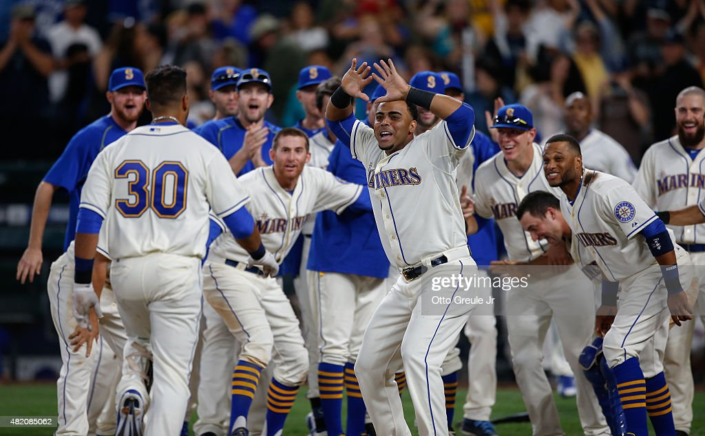 Franklin Gutierrez of the Seattle Mariners is congratulated by teammates after hitting a walkoff home run to defeat the Toronto Blue Jays 65 in ten...