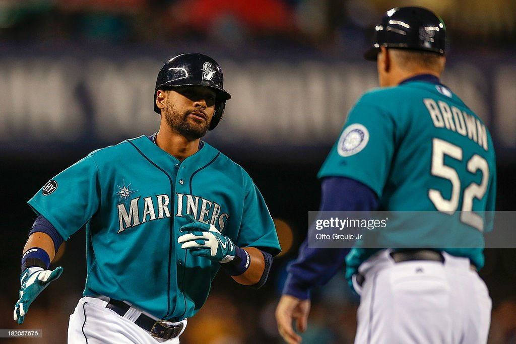 <a gi-track='captionPersonalityLinkClicked' href=/galleries/search?phrase=Franklin+Gutierrez&family=editorial&specificpeople=837650 ng-click='$event.stopPropagation()'>Franklin Gutierrez</a> #21 of the Seattle Mariners is congratulated by third base coach Daren Brown #52 after hitting a home run in the first inning against the Oakland Athletics at Safeco Field on September 27, 2013 in Seattle, Washington.