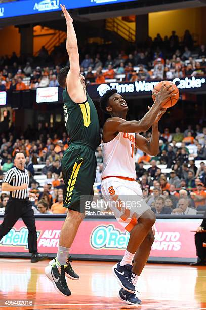 Franklin Howard of the Syracuse Orange drives to the basket against the defense of Connor Mahoney of Le Moyne Dolphins during the first half at the...