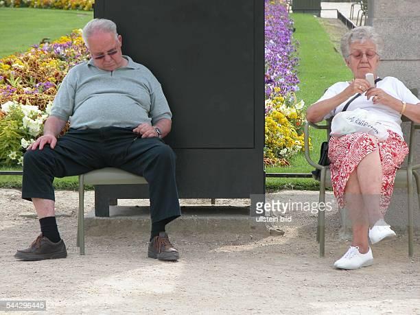 Entspannung im Jardin du Luxembourg älterer Mann hält ein Nickerchen ältere Frau beschäftigt sich mit ihrem Handy