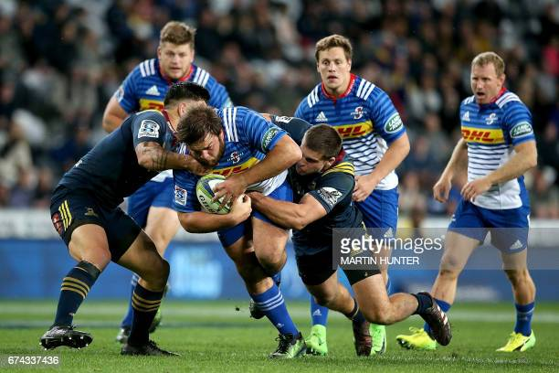 Frans Malherbe of the Western Stormers is tackled by Otago Highlanders' Malakai Fekitoa and Dillon Hunt during the Super Rugby match between the...