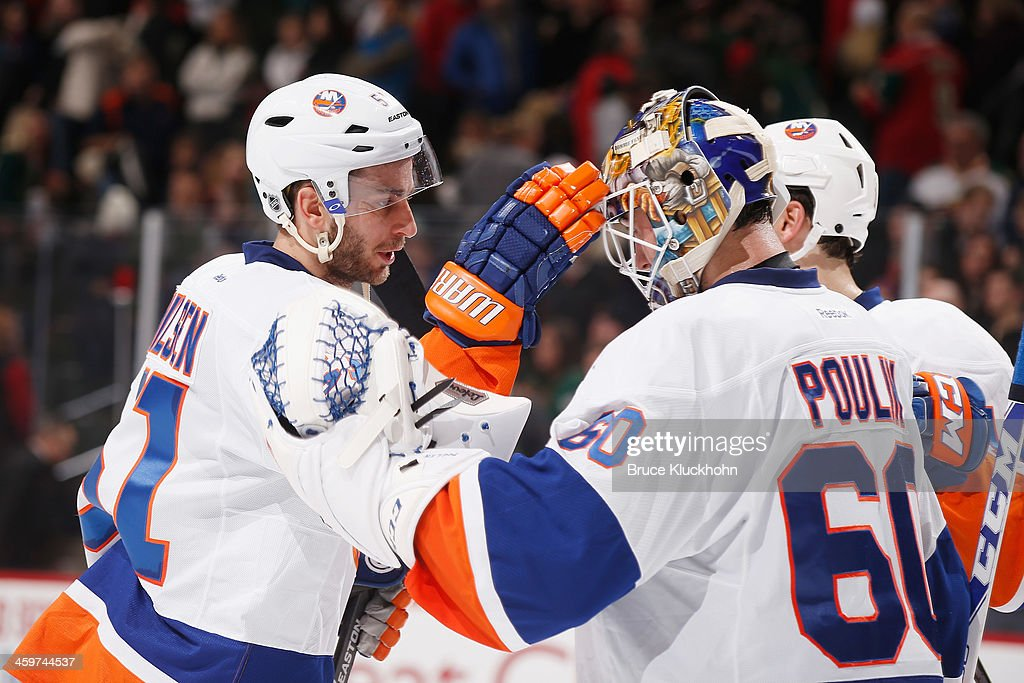 Frans Nielsen #51 and Kevin Poulin #60 of the New York Islanders celebrate after defeating the Minnesota Wild on December 29, 2013 at the Xcel Energy Center in St. Paul, Minnesota.