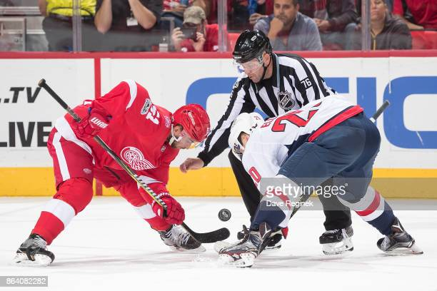 Frans Nielsen of the Detroit Red Wings faces off against Lars Eller of the Washington Capitals as linesman Michel Cormier drops the puck during an...