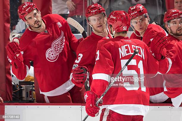 Frans Nielsen of the Detroit Red Wings pounds gloves with teammates on the bench following his second period goal during an NHL game against the...