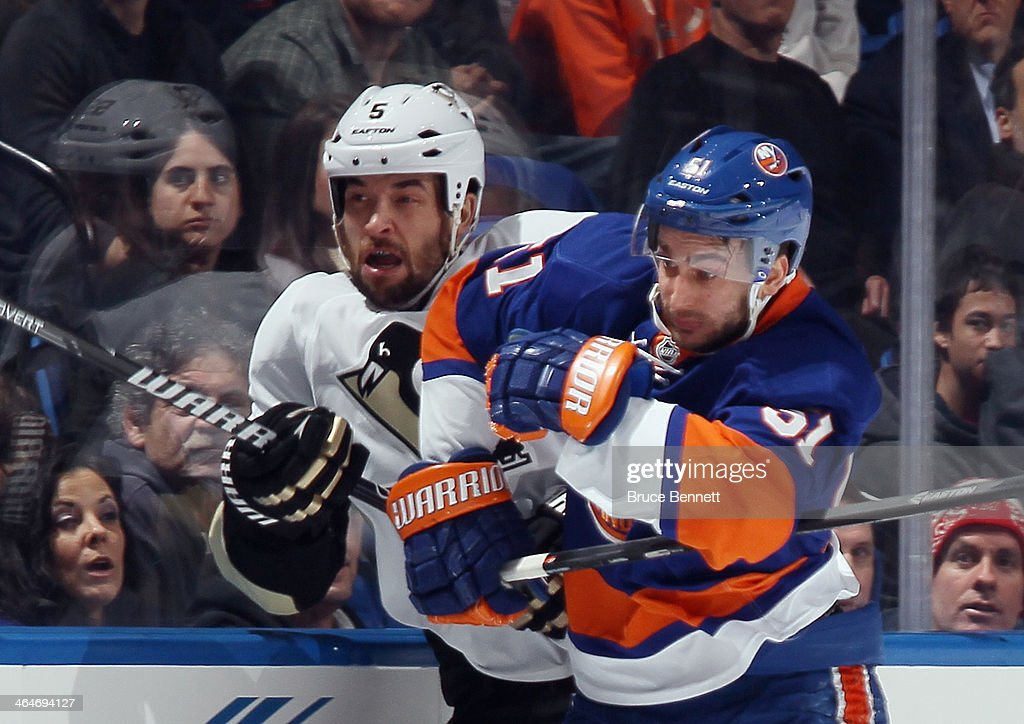 Frans Nielsen #51 of the New York Islanders checks Deryk Engelland #5 of the Pittsburgh Penguins into the boards during the first period at Nassau Veterans Memorial Coliseum on January 23, 2014 in Uniondale, New York.