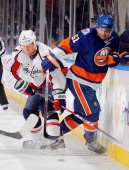 Frans Nielsen of the New York Islanders gets tangled with John Erskine of the Washington Capitals at Nassau Veterans Memorial Coliseum on November 5...