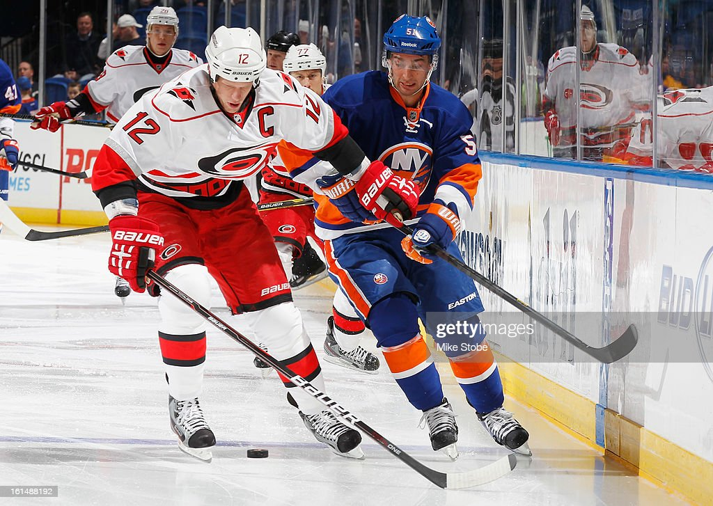 Frans Nielsen #51 of the New York Islanders is held off by Eric Staal #12 of the Carolina Hurricanes at Nassau Veterans Memorial Coliseum on February 11, 2013 in Uniondale, New York.