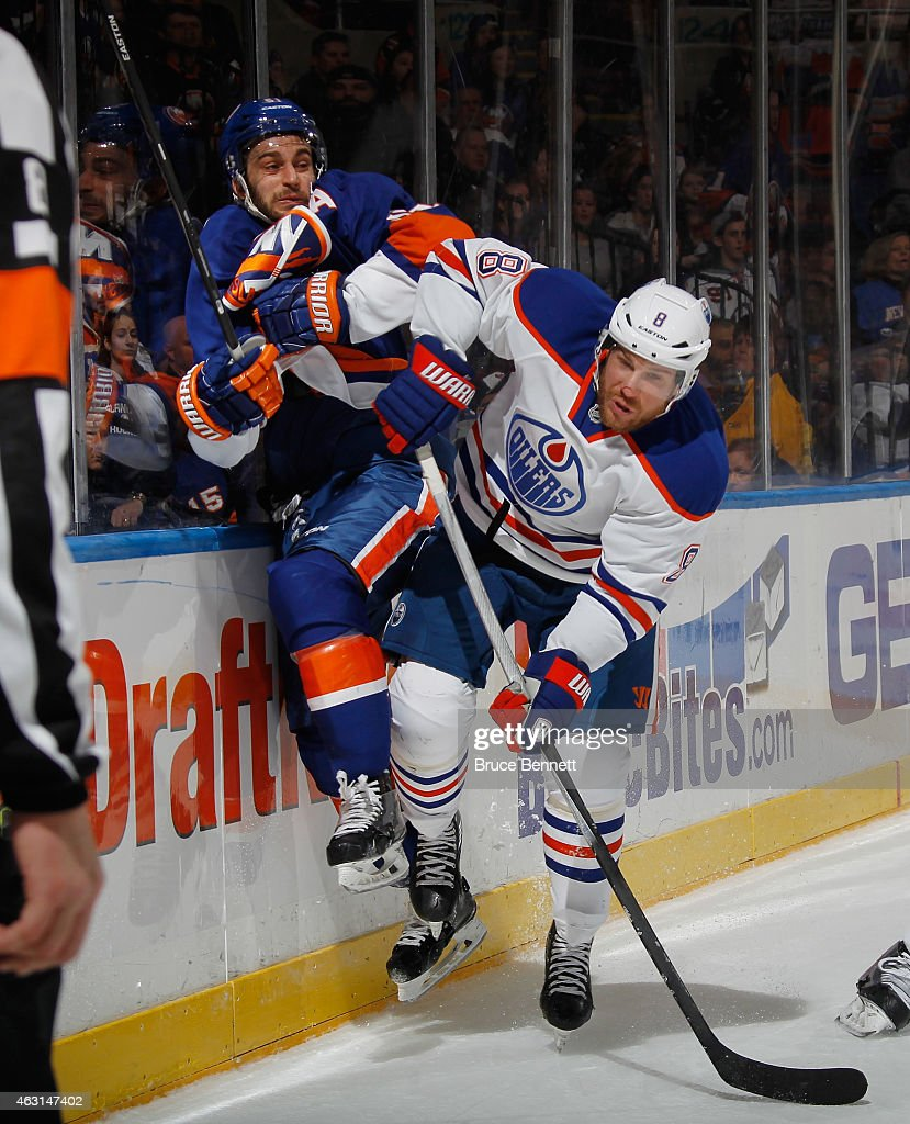 Frans Nielsen #51 of the New York Islanders is hit into the boards by Derek Roy #8 of the Edmonton Oilers during the second period at the Nassau Veterans Memorial Coliseum on February 10, 2015 in Uniondale, New York.
