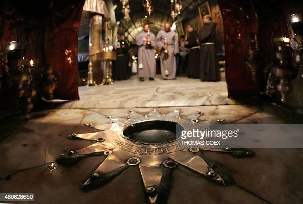 Fransciscan priests pray during a procession in front of the Bethlehem star inside the Grotto at the Church of the Nativity revered as the site of...