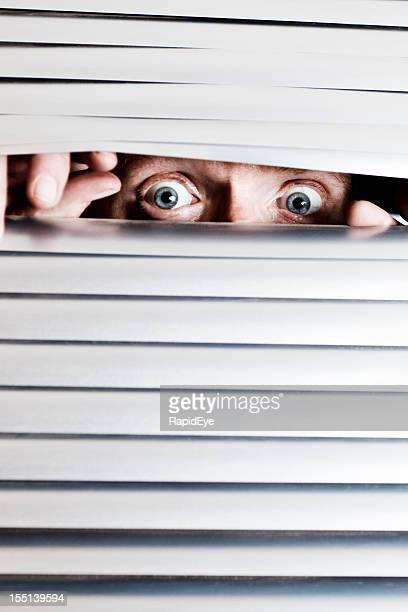 Frantic looking man's eyes peep through blinds at something terrifying