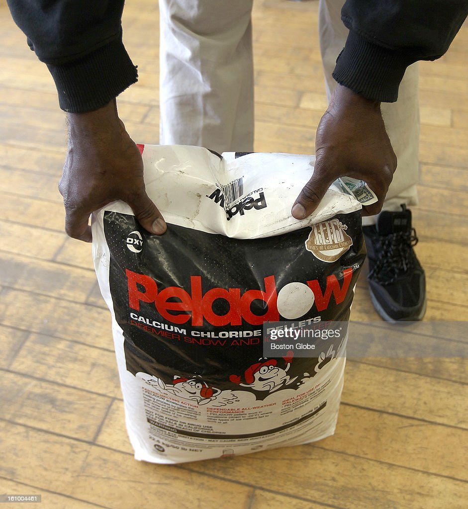 Frantz Theodore from Boston, buys a bag of ice melt at the Model Hardware Store in Allston to prepare for the upcoming storm.