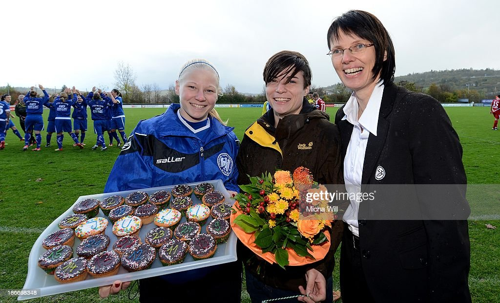 Franziska Thomas (L) of Wuerzburg hands over a tray with numbered cupcakes to Julia Manger (C) after Mager was honored as topscorer of season 2012/2013 of the 2nd FBL (Woman's Bundesliga) by Prof. Dr. Silke Sinning during the Second Bundesliga match between ETSV Wuerzburg and SC Sand at Sportpark Herieden on November 3, 2013 in Wuerzburg, Germany.