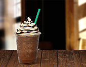 Frappuccino in takeaway cup on wooden table isolated on blackFrappuccino in takeaway cup on wooden table isolated on black