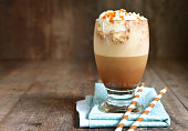 Frappuccino with caramel syrup and whipped cream in a glass on rustic background.