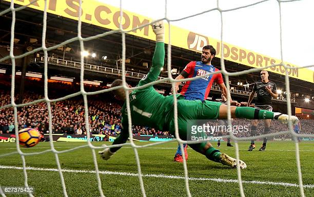 Fraser Forster of Southampton dives in vain as James Tomkins of Crystal Palace scores his team's second goal during the Premier League match between...