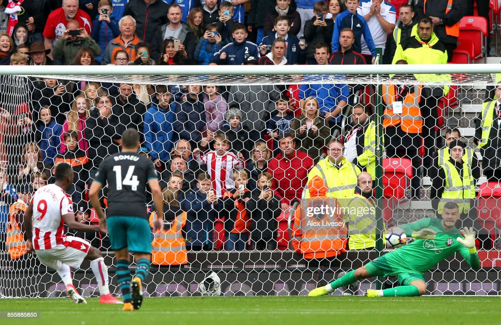 Fraser Forster of Southampton makes a save a penalty taken by Saido Berahino of Stoke City during the Premier League match between Stoke City and Southampton at Bet365 Stadium on September 30, 2017 in Stoke on Trent, England.