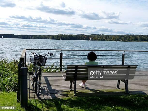 Frau auf einer Bank im Kurpark am Ufer vom Scharmützelsee in Bad Saarow