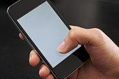 Eine Frauenhand hält ein Mobiltelefon Handy vor schwarzem Hintergrund. Der Bildschirm ist weiß ohne Inhalt. Der rechte Daumen berührt den Bildschirm im unteren Bereich.
