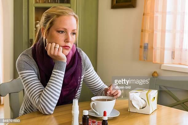 Frau im Krankenstand mit Tee und Medikamenten Erkältung Schnupfen und Grippezeit