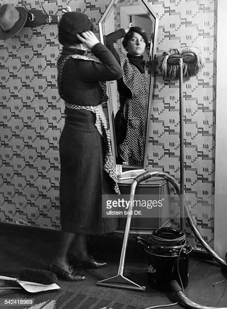 Frau mit Schürze vor dem Spiegel r ein Miele Staubsauger veröff Sieben Tage 12/1933