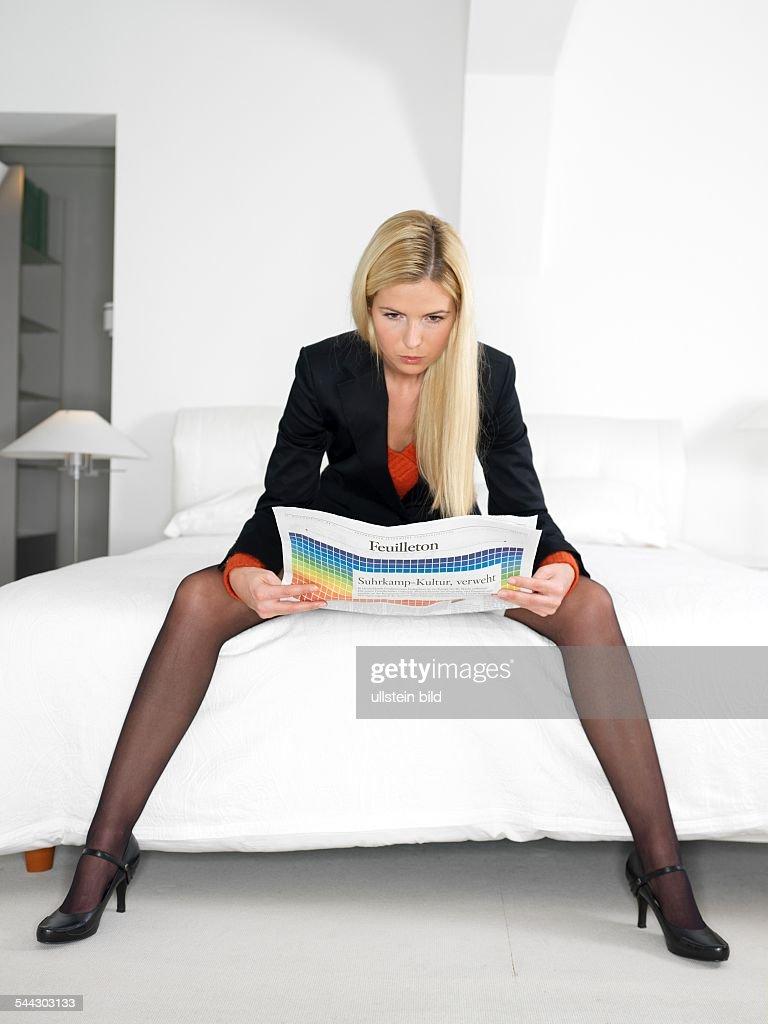 frau sitzt breitbeinig auf dem bett und liest zeitung ady reads pictures getty images. Black Bedroom Furniture Sets. Home Design Ideas