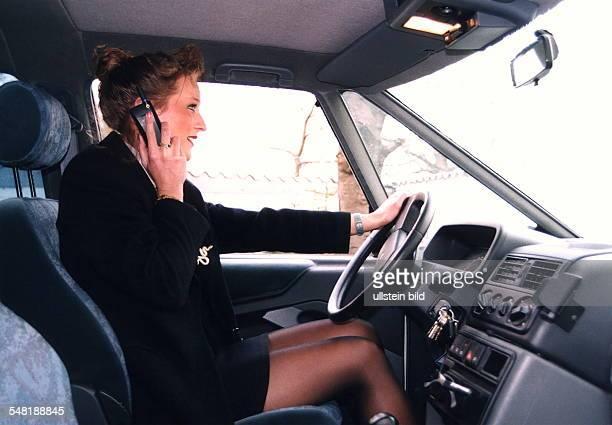 Frau sitzt im Auto hinter dem Lenkrad und telefoniert dabei mit einem Mobiltelefon 1996