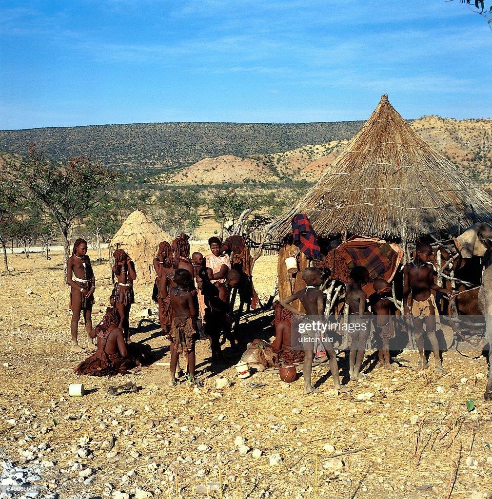 Frauen und Kinder der Himba intraditioneller Kleidung vor ihrem Dorfbei Opuwo 1995 col