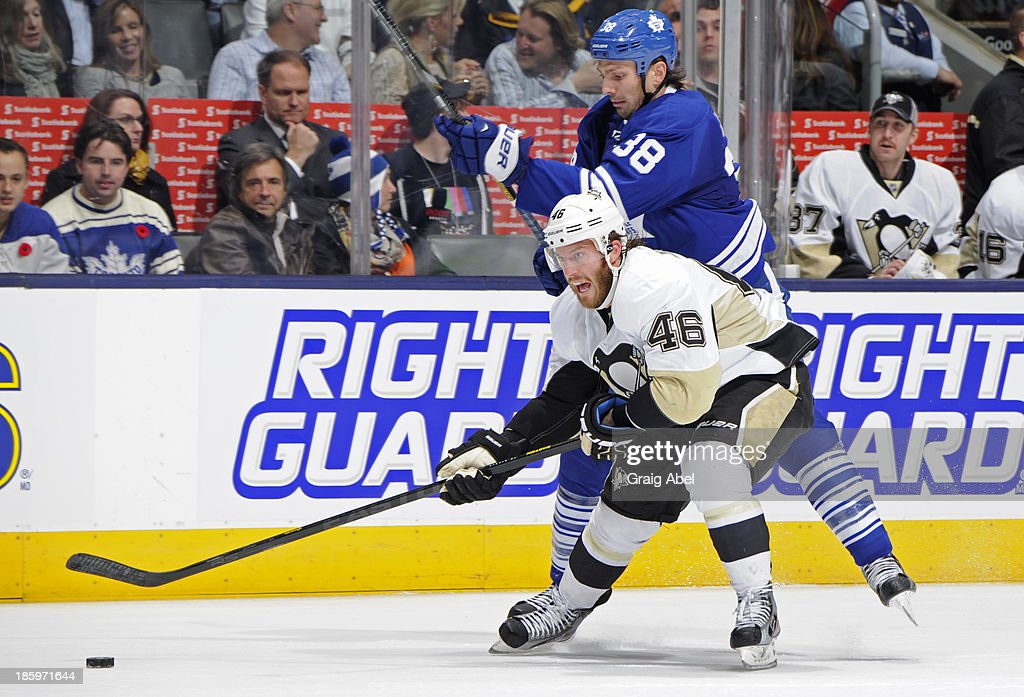Frazer McLaren #38 of the Toronto Maple Leafs battles for the puck with Joe Vitale #46 of the Pittsburgh Penguins during NHL game action October 26, 2013 at Air Canada Centre in Toronto, Ontario, Canada.