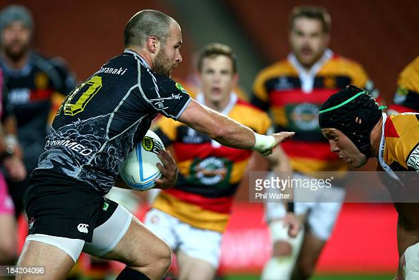 Frazier Climo of Taranaki fends off the Waikato defence during the round nine ITM Cup match between Waikato and Taranaki at Waikato Stadium on...
