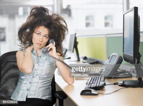 Frazzled businesswoman talking on telephone : Stock Photo