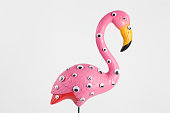 quirky and freak pink plastic flamingo on a pink background with numerous eyes'ngradient and tones on tones