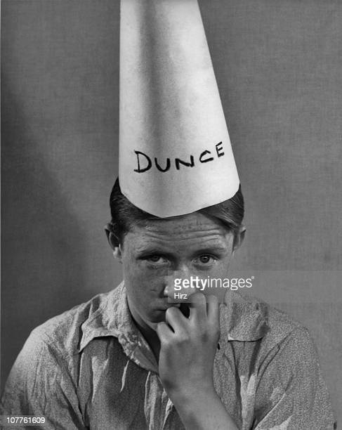 A freckled boy sitting against a wall wearing a 'Dunce' hat and holding his hand to his face in the 1950's