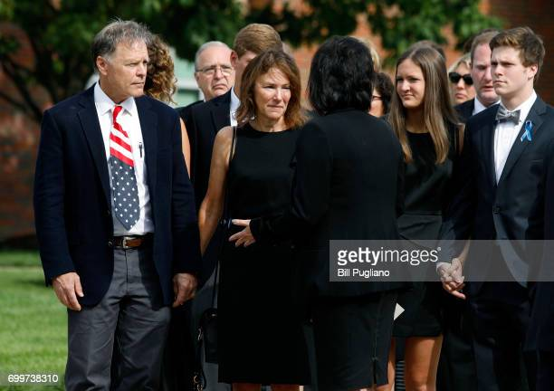 Fred and Cindy Warmbier talk with a woman after watching the casket of their son Otto Warmbier carried out from his funeral at Wyoming High School...