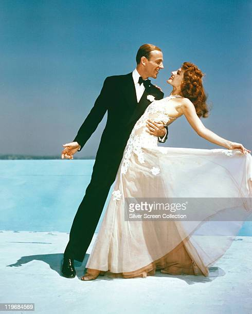 Fred Astaire US actor and dancer wearing a black dinner suit and bow tie and Rita Hayworth US actress and dancer wearing a flowing white evening gown...