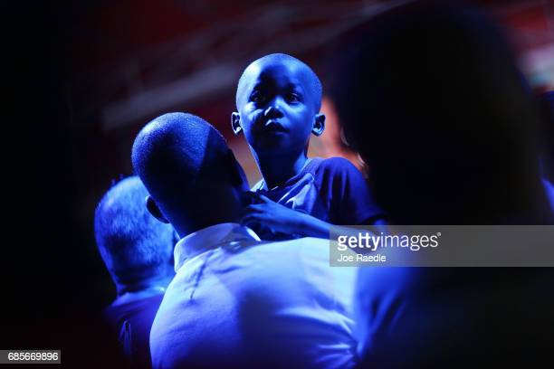Fred Augustin holds his son Matthan Augustin as they enjoy themselves at the 'Sounds of Little Haiti'concert at the Haitian Cultural Complex on May...