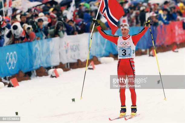 Fred Borre Lundberg of Norway holding the national flag crosses the finish line to win the gold medal in the Nordic Combined Team during day thirteen...