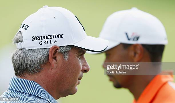 Fred Couples and Tiger Woods wait on the 13th green during the first round of the Memorial Tournament presented by Nationwide Insurance at Muirfield...