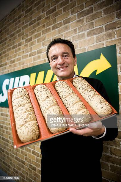 Fred DeLuca President and founder of sandwich maker Subway poses as he carries bread for sandwiches during an interview in front of a Subway...