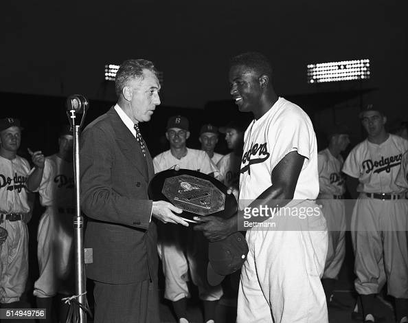 Fred Frick President of the National League presents Jackie Robinson star second baseman of the Brooklyn Dodgers with the gold plaque symbolizing his...