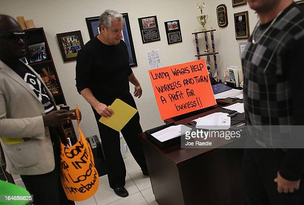 Fred Frost and other protesters leave a sign reading ' Living Wages Help Workers and Turn a Profit for business'' in the district office of Florida...