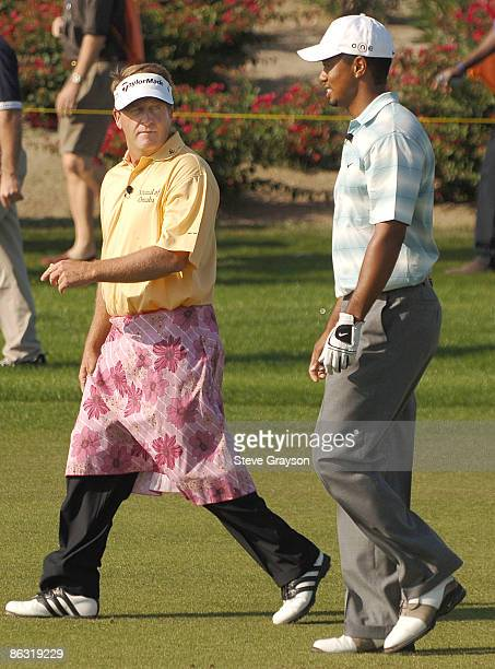 Fred Funk and Tiger Woods walks up the third fairway as he wears a skirt he received from Annika Sorenstam after Sorenstam outdrove him on the third...