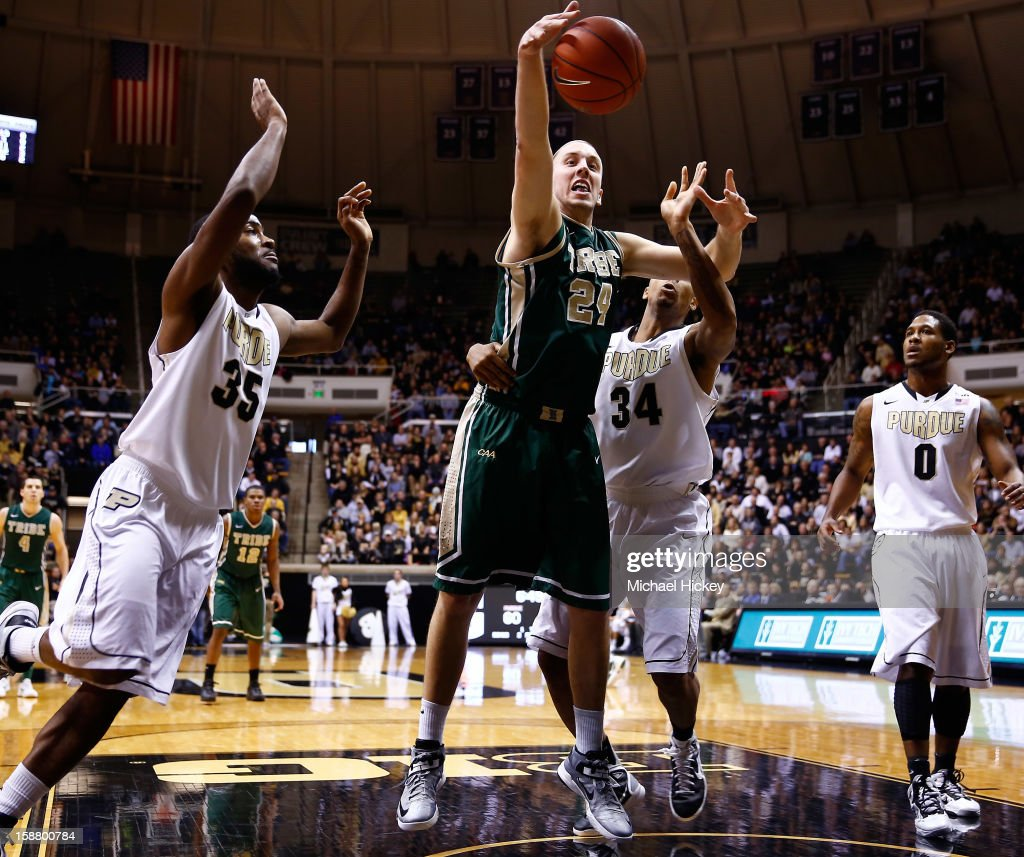 Fred Heldring #24 of the William & Mary Tribe reaches for the ball before going out of bounds as Rapheal Davis #35 and Jacob Lawson #34 of the Purdue Boilermakers defend at Mackey Arena on December 29, 2012 in West Lafayette, Indiana. Purdue defeated William & Mary 73-66.