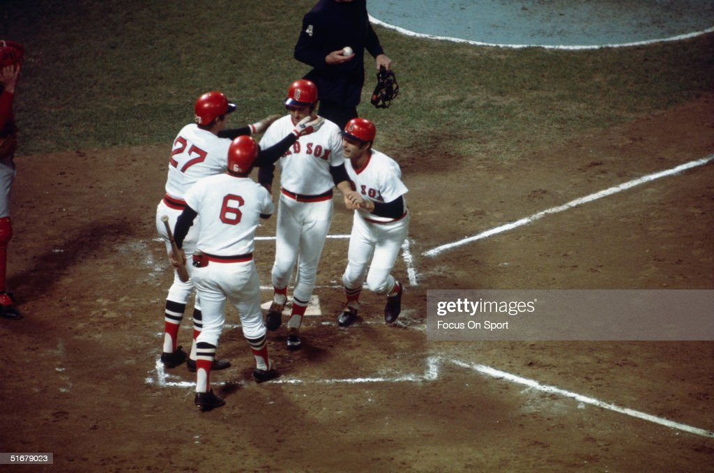Fred Lynn #19 of the Boston Red Sox crosses home plate after hitting a first inning home run as teammates Carl Yastrzemski #8, Carlton Fisk #27, and on-deck batter Rico Petrocelli #6 greet him during Game 6 of the World Series against the Cincinnati Reds on October 21, 1975 at Fenway Park in Boston, Massachusetts.