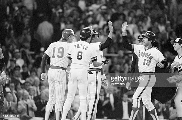 Fred Lynn of the California Angels has a big grin 7/6 as he is greeted by American League teammates after hitting grandslam homer the first in the...