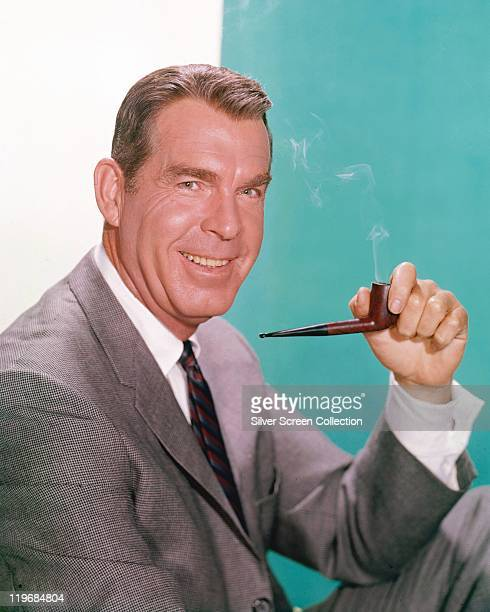 Fred MacMurray US actor smoking a pipe and wearing a grey suit white shirt and a redblueandblack striped tie in a studio portrait against a...